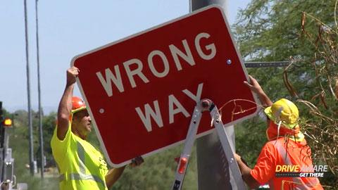 Two men putting up a Wrong Way sign